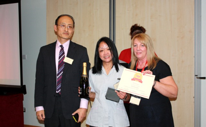 unitemps staff member awarding certificate and champagne tao asian lady