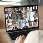 Woman on video call with colleagues on laptop