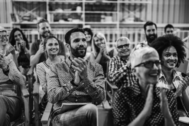 gathering of people sitting down smiling and clapping
